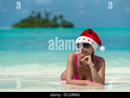 santa claus woman on beach - Stock Photo