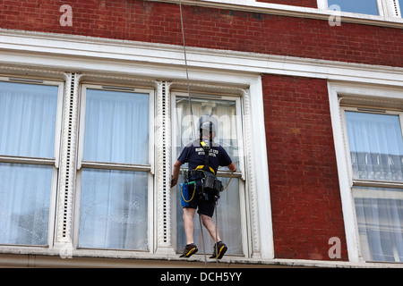 window cleaner using abseil rope London England UK - Stock Photo
