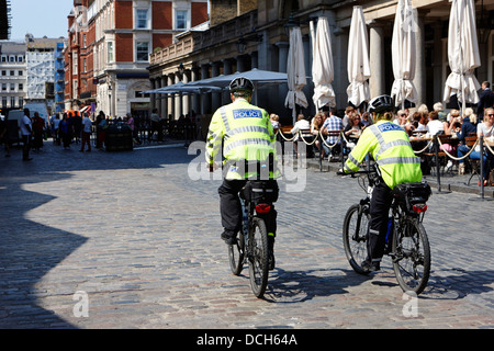 metropolitan police officers patrol covent garden on bikes London England UK - Stock Photo