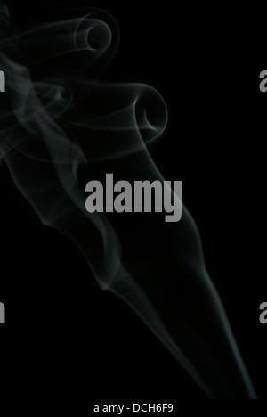 Sensitive incense smoke shape against black background - Stock Photo