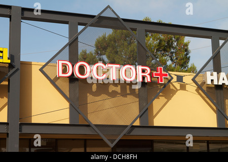 A doctors office sign with red cross in Santa Ana Southern California USA - Stock Photo