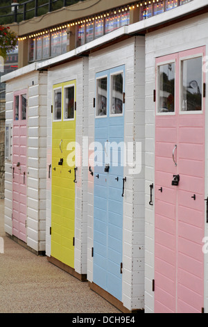 pastel coloued beach huts on promenade at Lyme Regis, Dorset in August - Stock Photo