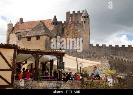 People eating at a restaurant below the Chateau de Beynac, Beynac-et-Cazenac, the Dordogne, France Europe - Stock Photo