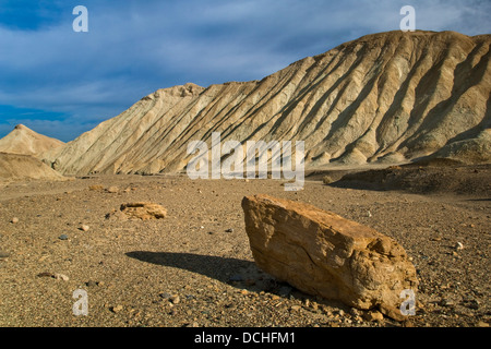 Lone rock below eroded hillside, Twenty Mule Team Canyon, Death Valley National Park, California - Stock Photo