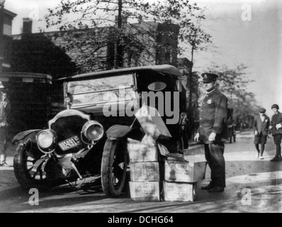Policeman standing alongside wrecked car and cases of moonshine, during USA Prohibition circa 1922 - Stock Photo