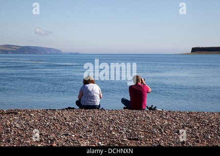 Dolphin watchers looking out to sea at Chanonry Point, Tourists watching the Moray Firth Bottlenose Dolphins, Cromarty, - Stock Photo