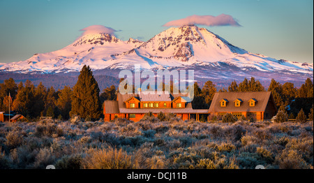 Ranch and the South and North Sister peaks in Oregon behind it - Stock Photo