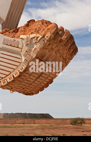 Open pit gold mining in Mauritania. Close up of giant excavator bucket carrying ore. West Africa - Stock Photo