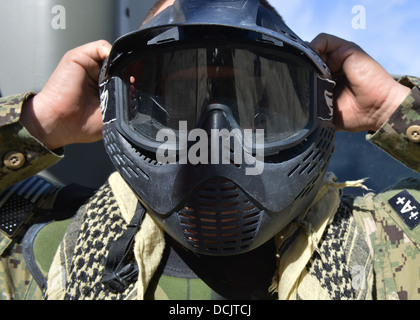 A US Navy sailor dons a face mask prior to force-on-force paintball training during a combined field-training exercise - Stock Photo