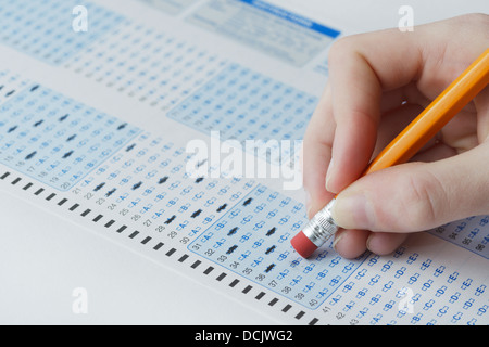 Optical scan answer sheet for a school exam with student erasing answer - Stock Photo