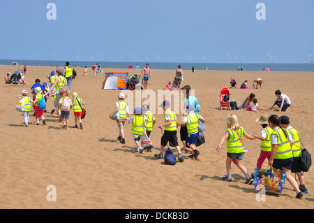 group of school children walking on the beach, Skegness, Lincolnshire, England, UK - Stock Photo