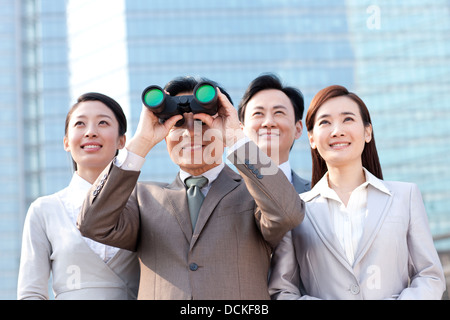 Professional business team looking with binoculars - Stock Photo