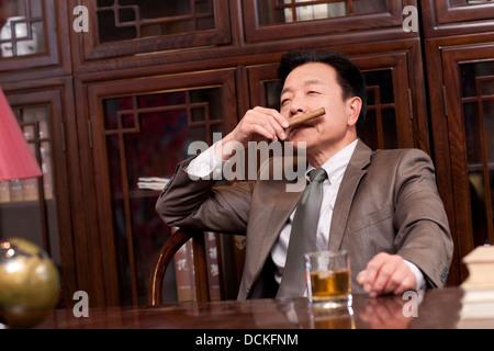 Successful businessman enjoying cigar - Stock Photo