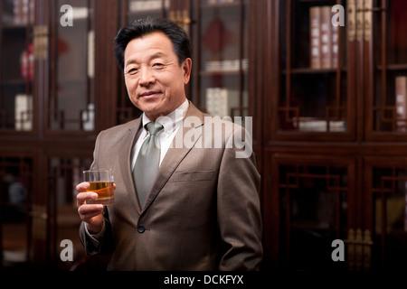 Successful businessman enjoying wine - Stock Photo
