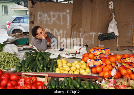 A vegetable and fruit seller sleeping at her stall in Tirana, Albania - Stock Photo
