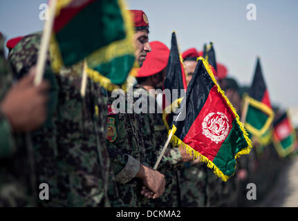 Afghan National Army stand in formation with flags during the national anthem at a celebration marking Afghan Independence - Stock Photo