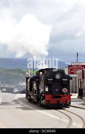 Welsh Highland Railway train hauled by a Beyer-Garratt engine crosses the road near Porthmadog Harbour station. - Stock Photo