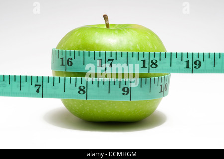 tape measure wrapped around green apple - Stock Photo