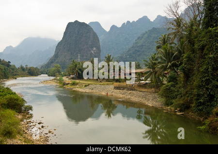 Horizontal view of traditional stilted wooden huts and homes along the banks of the Nam Song river close to Vang - Stock Photo