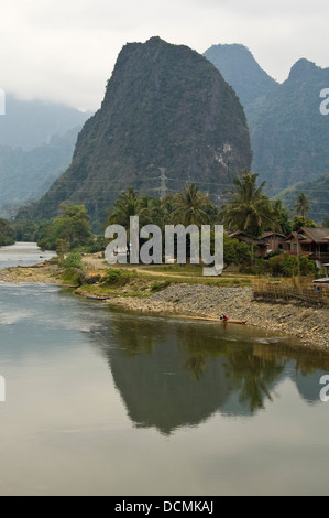 Vertical view of traditional wooden huts and homes along the banks of the Nam Song river close to Vang Vieng - Stock Photo
