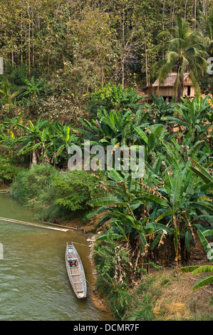 Vertical view of ramshackled hut and fishing boat along the banks of the Nam Song river close to Vang Vieng - Stock Photo