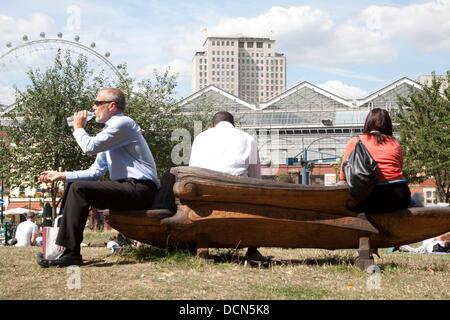 20th August 2013. Waterloo London UK. Office workers taking a lunch break outdoors near Waterloo station as Londoners - Stock Photo