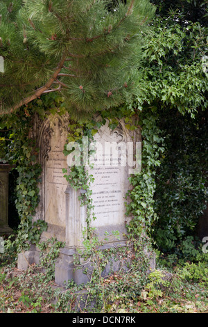 Old headstone covered with ivy and trees, Arno's Vale Cemetery, Bristol, England - Stock Photo