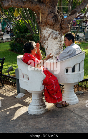 Elderly woman and younger man sitting and chatting in love seats in the main square of Merida, Yucatan, Mexico - Stock Photo