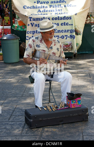 Older street musician playing a musical saw or singing saw in Merida, Yucatan, Mexico - Stock Photo