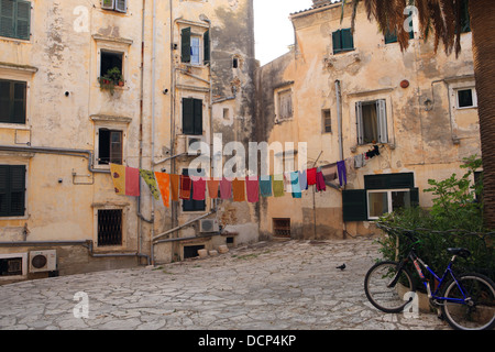 Colourfu washing hanging in a cobbled courtyard in Corfu Town in Greece - Stock Photo