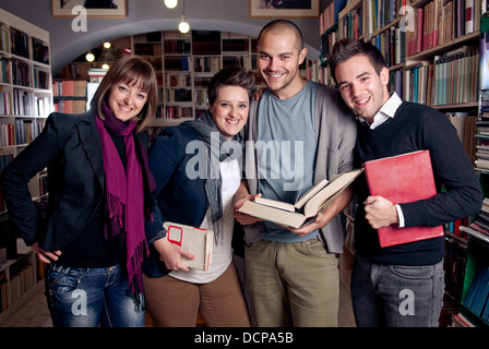 Group of students at a library smiling and holding books - Stock Photo