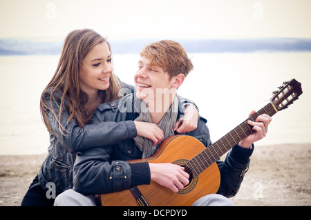 Young man with acoustic guitar and his girlfriend on the beach - Stock Photo