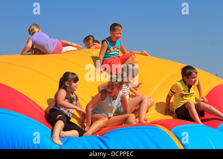 Happy children playing on giant plastic bubble during air show picnic in Katowice, Poland. - Stock Photo