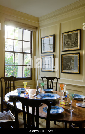 Venetian glassware on wooden table in dining room with collection of Hogarth's engravings on the wall - Stock Photo