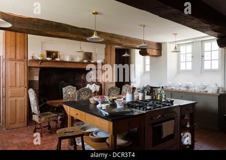 Island hob unit in kitchen with wooden ceiling beams and large open fireplace - Stock Photo