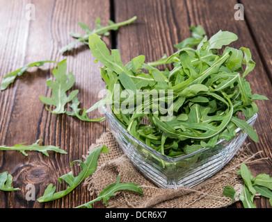 Fresh Arugula Salad on wooden background - Stock Photo