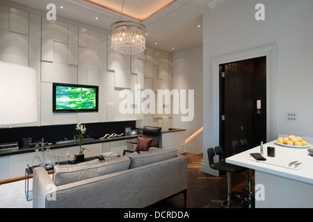 Seating area with glass chandelier in London city apartment - Stock Photo