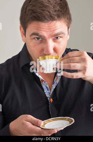 Businessman in black unbuttoned shirt relaxing with a cup of coffee