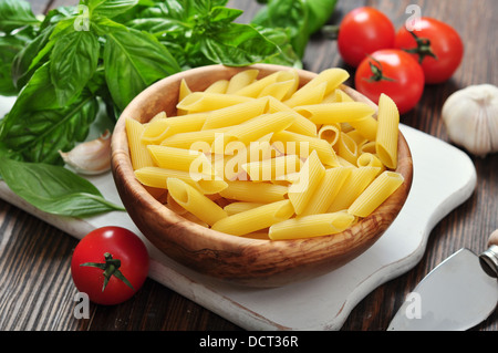 Penne Pasta and tomatoes with basil on wooden cutting board - Stock Photo