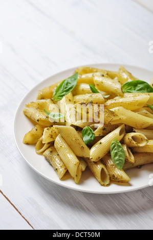 Penne pasta with pesto sauce and basil on white plate - Stock Photo