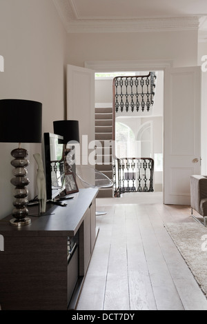 Matching lamps with flatscreen on sideboard in room with view of bansiter, Kensington - Stock Photo