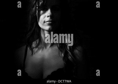 Black and white mysterious portrait of woman in bra - Stock Photo