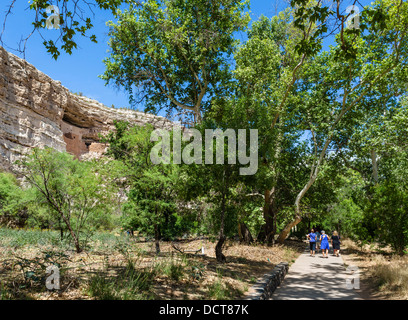 Tourists on trail at Montezuma Castle National Monument, well preserved cliff dwelling of the Sinagua, Camp Verde, - Stock Photo