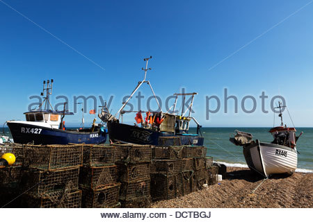 Shore launched fishing boat and piled lobster pots high on the shingle beach of Hastings, East Sussex, England. - Stock Photo