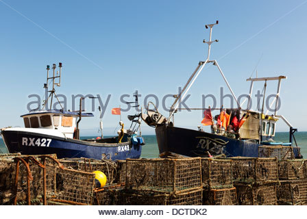 Shore launched fishing boat2 high on the shingle beach and surrounded by crab and lobster pot, Hastings, East Sussex, - Stock Photo