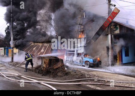 Fireman controlling a huge fire - Stock Photo