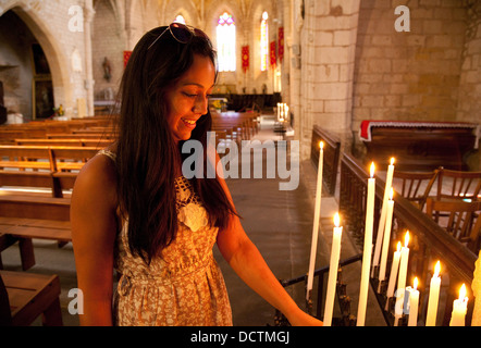Teenage girl lighting a candle in church, Monpazier, Dordogne, France Europe - Stock Photo