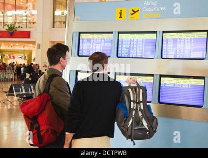 Travellers Studying Flight Departure Screens, Costa Del Sol, Malaga, Spain - Stock Photo