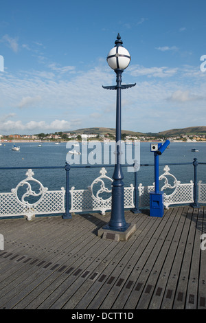 A view across Swanage pier and the bay with a lamppost and blue telescope on the deck - Stock Photo