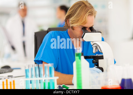 male scientist looking through microscope in the lab - Stock Photo